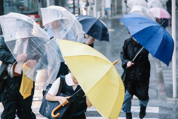 大雨と強風にさらされる人たち
